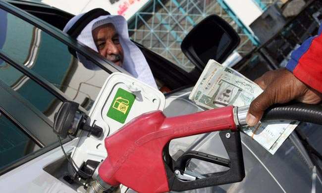 A foreign worker at a petrol station fills up a Saudi man's car north of Riyadh, 31 October 2007. The price of oil fell from record highs to below 90 dollars per barrel in Asian trade today as investors profited on expectations of an increase in US crude stocks, dealers said. AFP PHOTO/HASSAN AMMAR (Photo credit should read HASSAN AMMAR/AFP/Getty Images)